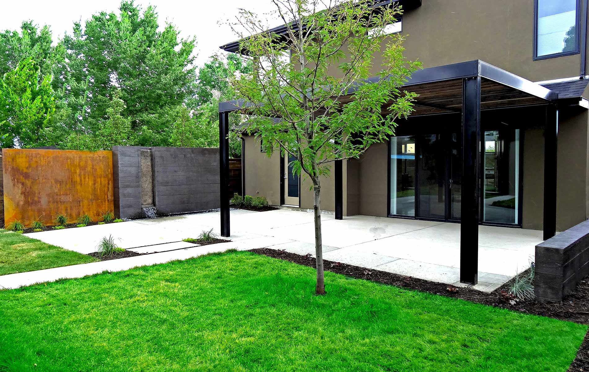 Large steel and wood arbor over patio in Modern Steel Arbor and Poured Concrete Water Feature in Denver's Highlands Mile High Landscaping in Denver