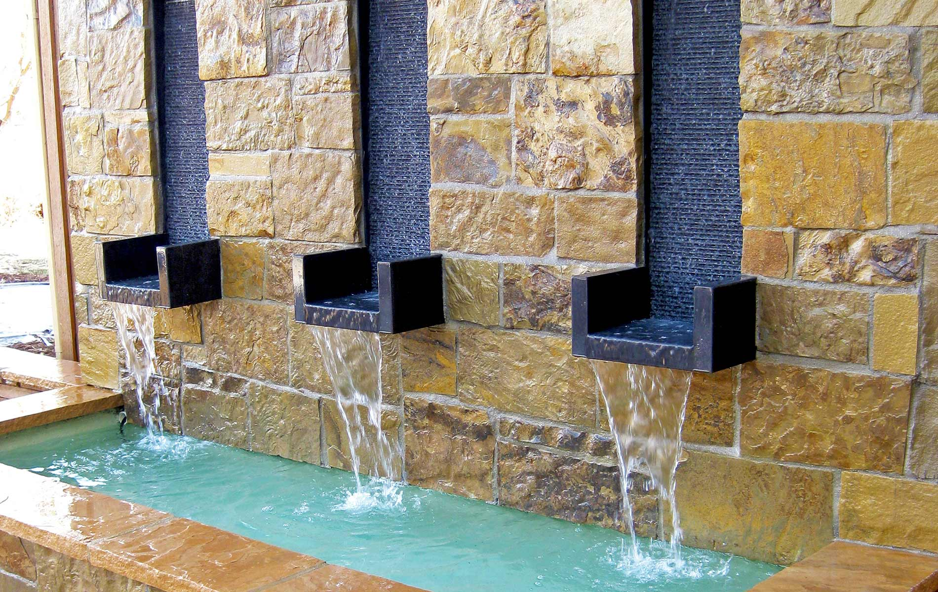 custom water wall softens the sound of this rustic patio